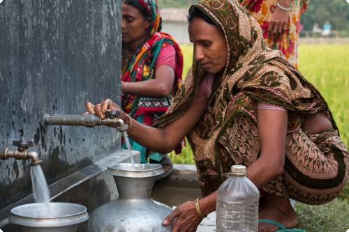 Femmes remplissant des jarres d'eau en zone rurale d'Asie