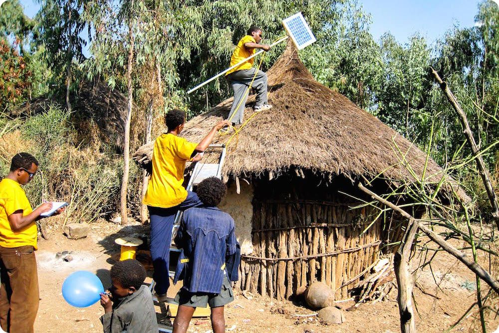 Technician installing a solar panel on a rural house, solar village project