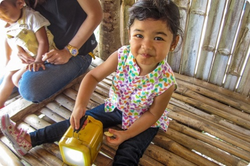 Child playing with a solar lantern in Philippines, HSSI project