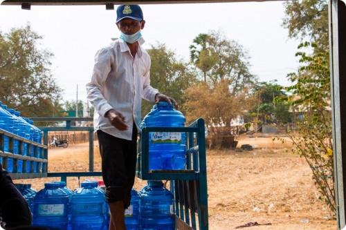 Cambodgien transportant des bouteilles de 20L d'eau