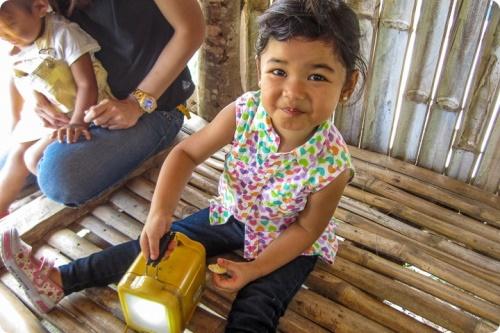 Petite fille jouant avec une lampe solaire aux Philippines, projet de HSSI