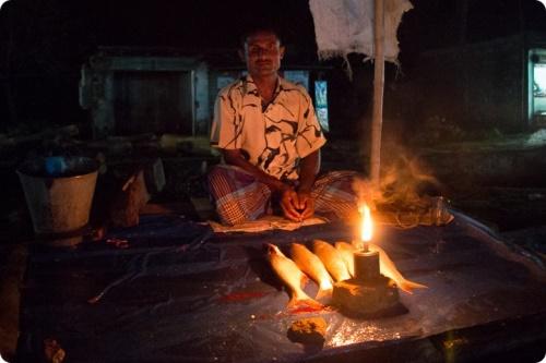 Vendeur de poisson au Cambodge s'éclairant avec une lampe à kérosène