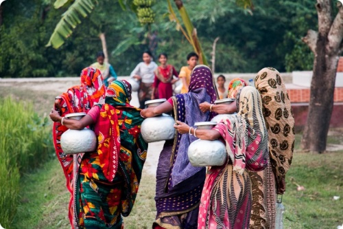 Women carrying water jugs in a rural area